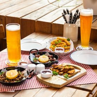 Leckeres fleischmahlzeiten-roulette mit zitrone, sprotte und bier auf dem tisch im restaurant