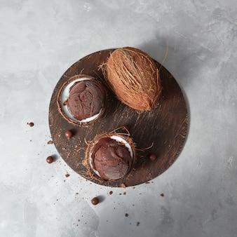 Leckeres frisches grünes fruchtsorbet in kokosnussschale mit ganzer frischer kokosnuss auf einem brett auf einem grauen tisch