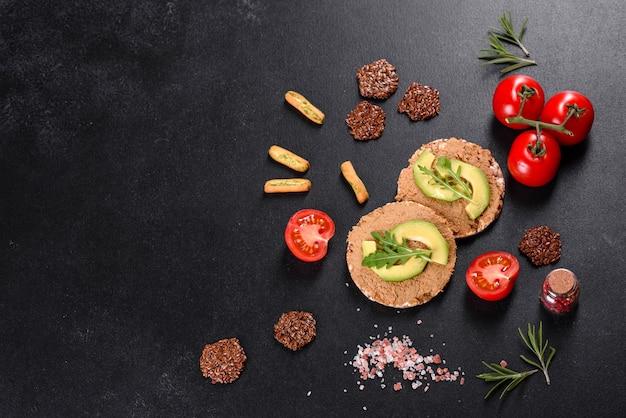 Leckeres frisches sandwich mit leberpaste, avocadostücken und rucola auf einem dunklen betontisch
