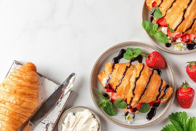 Leckeres frühstück. croissants mit frischen erdbeeren, frischkäse, minze und schokoladensauce auf weißem hintergrund. ansicht von oben