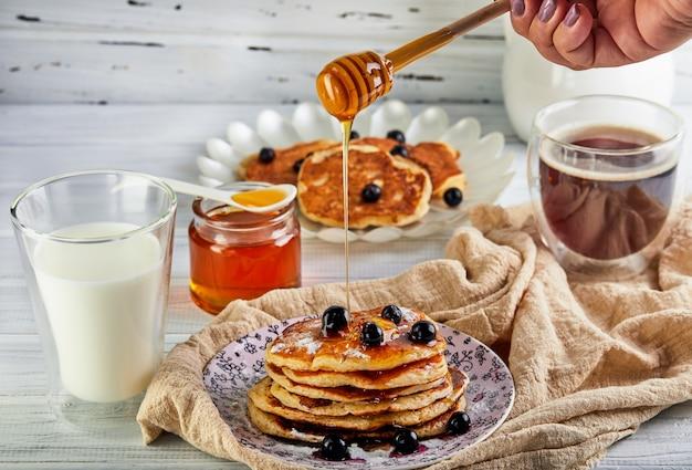 Leckeres frühstück. ein stapel pfannkuchen mit honigsirup ein glas milch, espressokaffee und honig auf einem hölzernen weiß