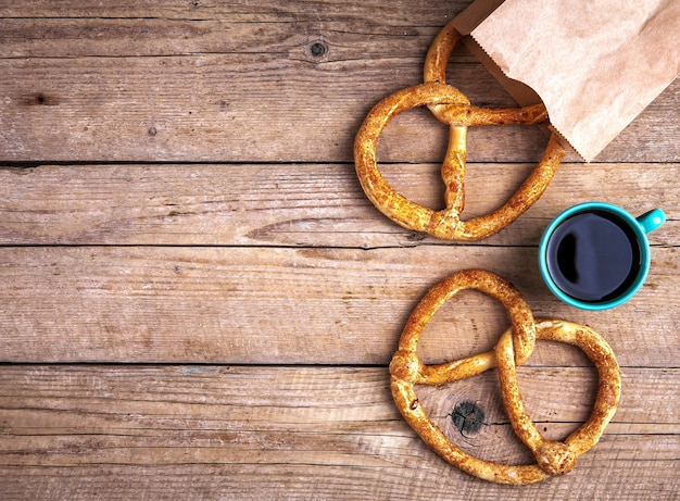 Leckeres frühstück, eine brezel mit kaffee auf hölzernem hintergrund. das essen, die getränke. und