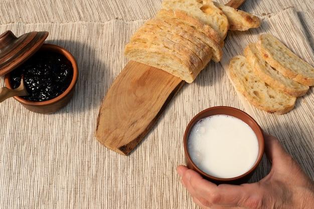 Leckeres frühstück. frisches brot mit marmelade und milch. milch wird in eine tasse gegossen. toast mit marmelade auf serviette. ausgewogenes essen.