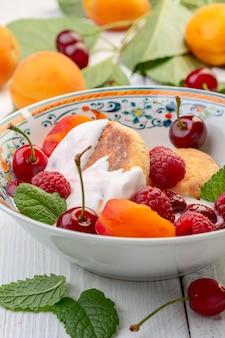 Leckeres frühstück - hüttenkäsekrapfen, hüttenkäsepfannkuchen mit himbeeren, kirschen, aprikosen und sahnesauce in einem weißen teller, selektiver fokus.