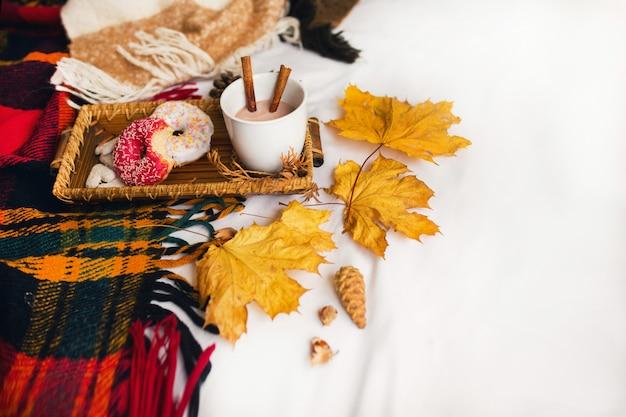 Leckeres frühstück im bett auf holztablett mit tasse kakao, zimt, keksen und glasierten donuts.