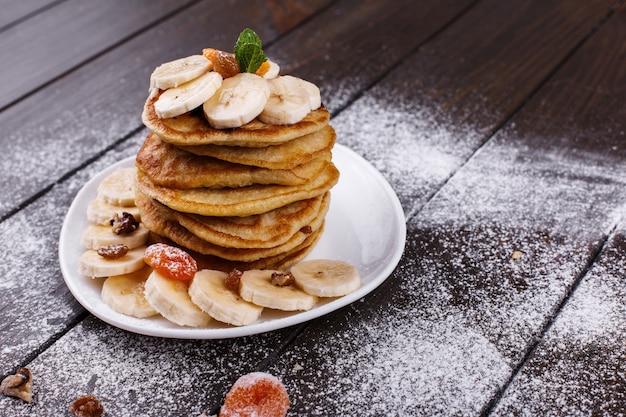Leckeres frühstück. köstliche puncakes mit bananen, nüssen und minze dienten auf weißer platte