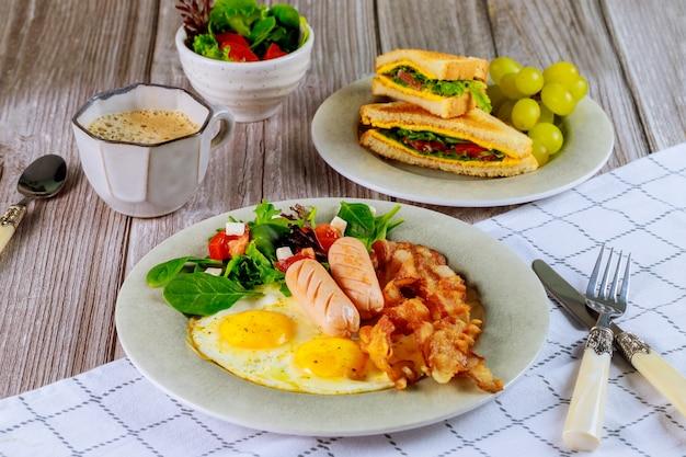 Leckeres frühstück mit eiern, würstchen, speck und einer tasse kaffee.