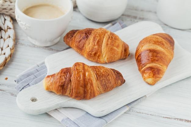 Leckeres frühstück mit frischen croissants und einer tasse kaffee auf weißem holz. leckeres backen
