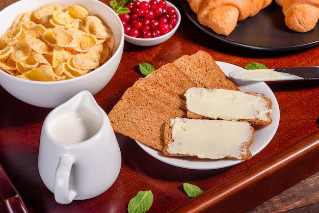 Leckeres frühstück mit frischen croissants und reifen beeren auf einem schönen holztisch
