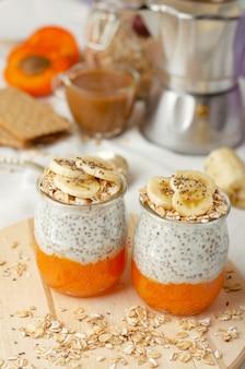 Leckeres frühstück mit kaffee, chiasamenpudding mit banane, zertrümmerten frischen aprikosen- und hafermahlzeiten