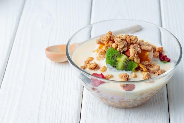 Leckeres frühstück mit müsli, joghurt und obst in einer glasschüssel