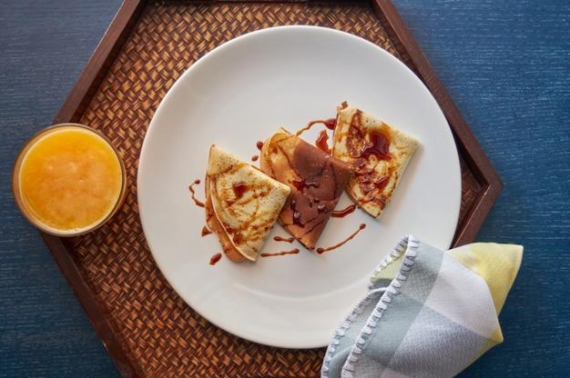 Leckeres frühstück mit pfannkuchen und orangensaft auf holztablett