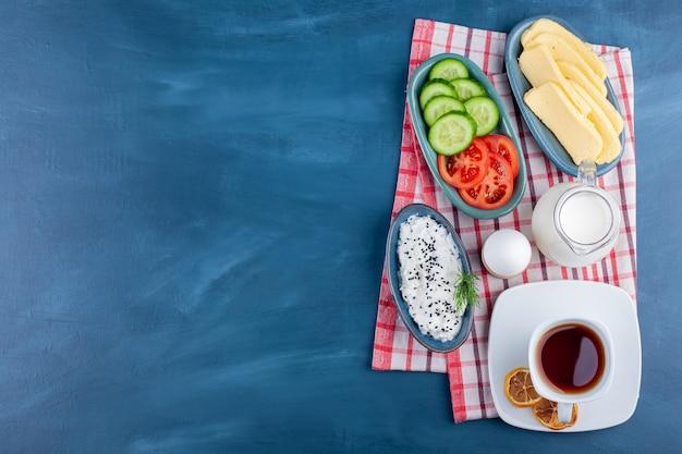 Leckeres frühstück mit tee, milch und käse auf blauer oberfläche.