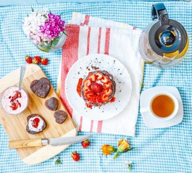 Leckeres frühstück mit teller mit pfannkuchen und erdbeeren