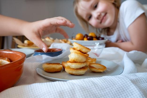 Leckeres frühstück mit winzigen mini-pfannkuchen, kirschen, aprikosen, marmelade auf einem weißen tisch
