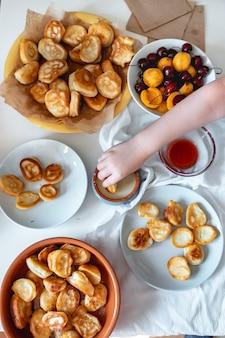 Leckeres frühstück mit winzigen mini-pfannkuchen-kirschen-aprikosen-marmelade