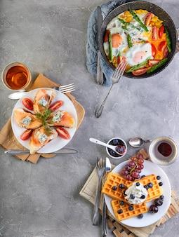 Leckeres frühstück. rührei in einer pfanne, sandwiches mit stroh und käse und belgische waffeln auf einem hölzernen weiß