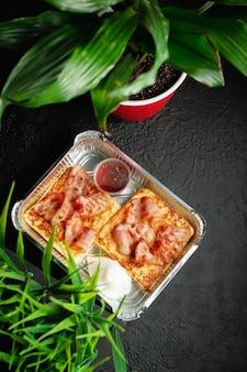 Leckeres frühstück. rührei mit speck auf dunklem holzhintergrund