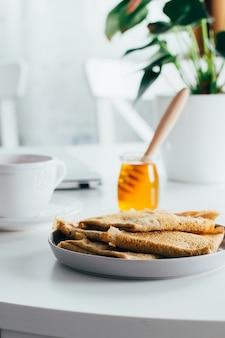 Leckeres frühstück. weiße tischplatte mit laptop und frischen krepppfannkuchen, tasse tee