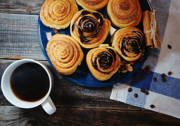 Leckeres frühstück, zimtschnecke mit schokoladenüberzug und eine tasse kaffee Premium Fotos