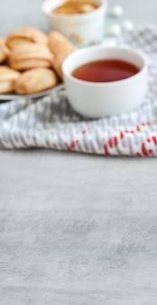 Leckeres frühstückskonzept. vertikales banner mit kopierraum und defokussierter tasse tee mit süßen zimtplätzchen auf der oberfläche. flache tiefe