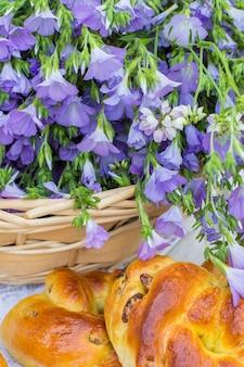 Leckeres gebäck (brötchen mit rosinen) und bouquet-leinen im weidenkorb