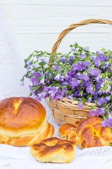 Leckeres gebäck (brot und brötchen mit rosinen) und bouquet-leinen im weidenkorb