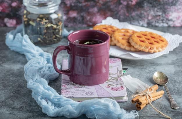 Leckeres gebäck mit einer tasse tee und zimtstangen.