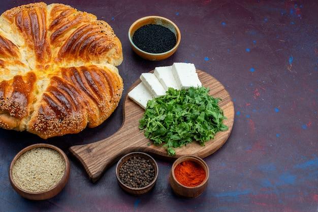 Leckeres gebäck mit halber draufsicht, gebacken mit gemüse und weißem käse auf dunklem hintergrund.