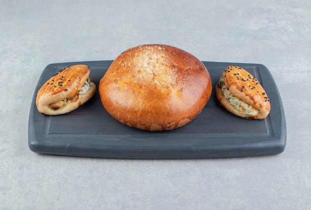 Leckeres gebäck mit käse und brötchen auf schwarzem brett.
