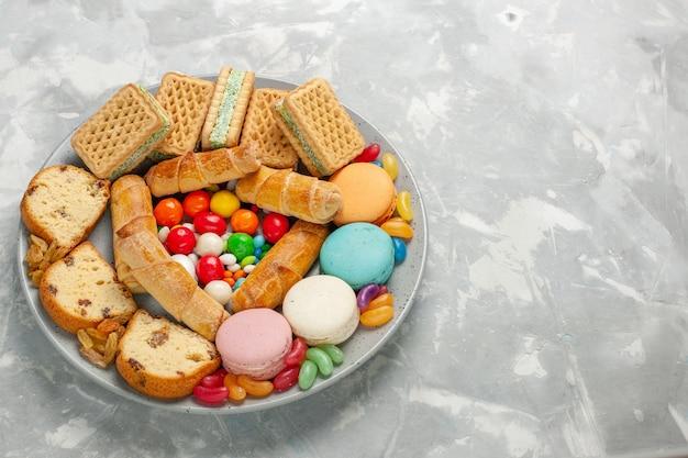 Leckeres gebäck mit macarons und süßigkeiten auf weißem tisch