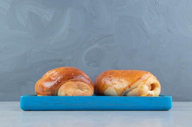 Leckeres gebäck mit würstchen auf blauem brett.