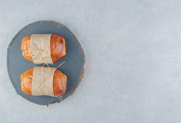 Leckeres gebäck mit würstchen auf holzstück.