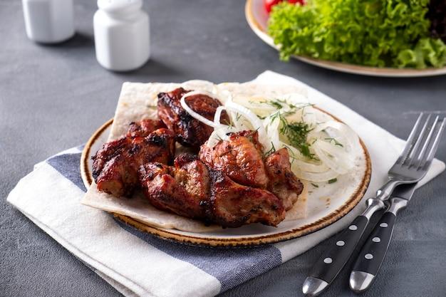 Leckeres gegrilltes fleisch mit zwiebeln auf einem teller kebabs