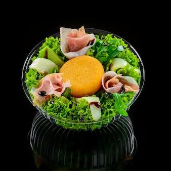 Leckeres gemischtes salatgericht mit gegrilltem camembertkäse, schinken, bio-tomaten und frischen grünen blättern. gesunde fleißige mahlzeit.