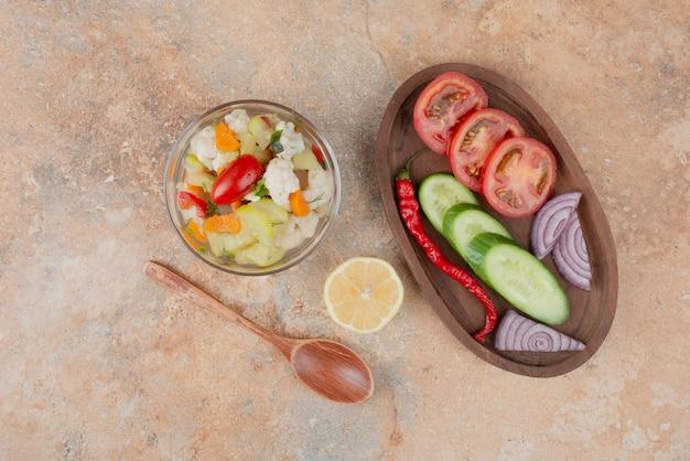 Leckeres gemüse auf glasplatte mit holzbrett aus tomaten, gurken und zwiebeln auf marmoroberfläche
