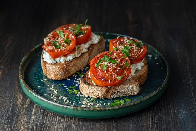 Leckeres geröstetes brot mit gerösteten roten tomaten, feta-käse, sesam und kräutern auf teller, nahaufnahme