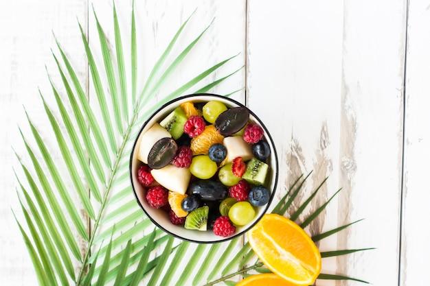 Leckeres gesundes frühstück mit einer mischung aus gehackten früchten und beeren in einer schüssel. ansicht von oben.