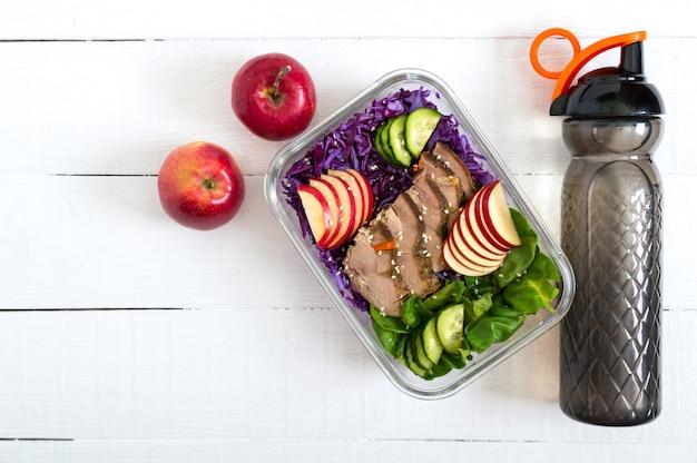 Leckeres gesundes mittagessen mit gemüse, gebackenem truthahn und einer flasche wasser. salat aus rotkohl, spinat, äpfeln, frischen gurken mit diätfleisch in einer glas-lunchbox auf einer weißen holzoberfläche.