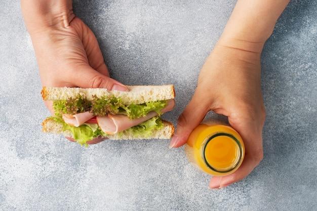 Leckeres gesundes sandwich für ein snack-frühstück in frauenhänden. toastbrot tomaten-schinken-blattsalat, saft in einer flasche,