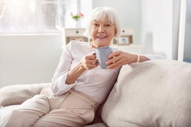 Leckeres getränk. fröhliche ältere frau, die auf dem sofa in ihrem wohnzimmer sitzt und eine tasse kaffee hält, während sie lächelt