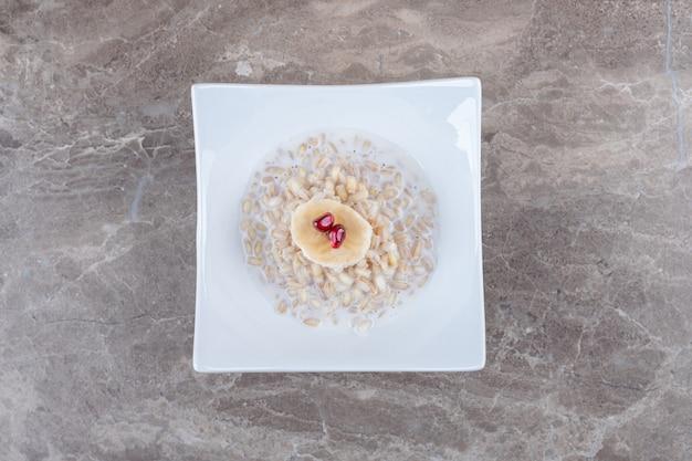 Leckeres granatapfel-aril auf dem zerbrochenen reiskuchen auf der marmoroberfläche