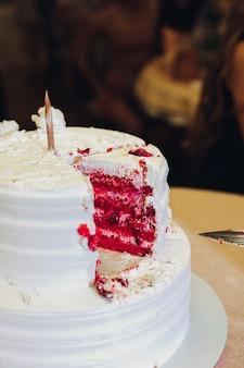 Leckeres großes appetitanregendes frisches stück des überlagerten kekskuchens der nahaufnahme bedeckt durch schlagsahnezuckerglasur. roter samt
