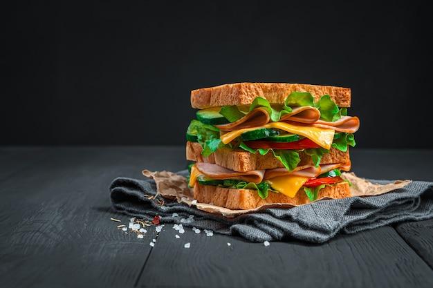 Leckeres großes sandwich mit schinken, gemüse und salat auf schwarzem hintergrund. seitenansicht, platz zum kopieren. fast food.