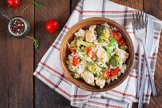 Leckeres hähnchen, brokkoli, grüne erbsen, tomatenpfanne mit reis. asiatische küche.