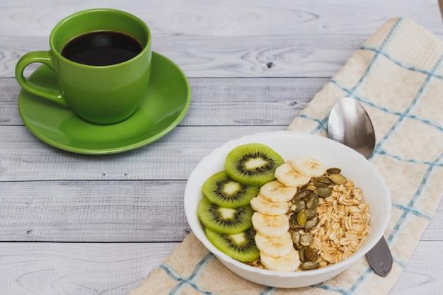 Leckeres haferflocken mit früchten und einer tasse kaffee auf einem holztisch. gesundes frühstück