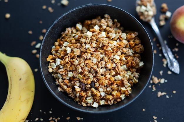 Leckeres hausgemachtes fruchtiges müsli-müsli, serviert in einer schüssel auf dunklem hintergrund. nahaufnahme