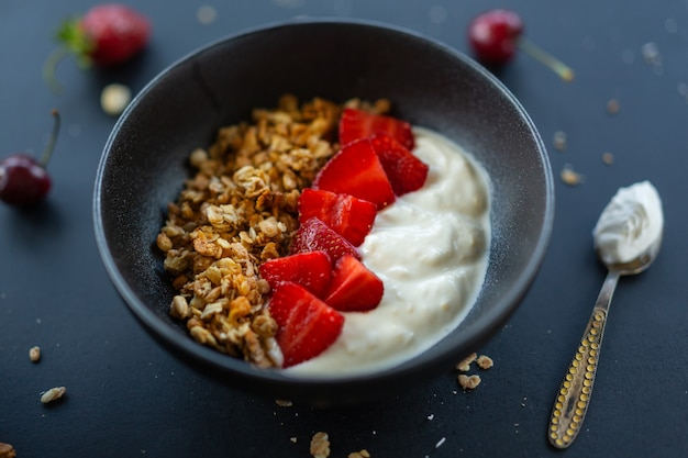 Leckeres hausgemachtes fruchtiges müsli-müsli, serviert in einer schüssel mit joghurt auf dunklem hintergrund. nahaufnahme