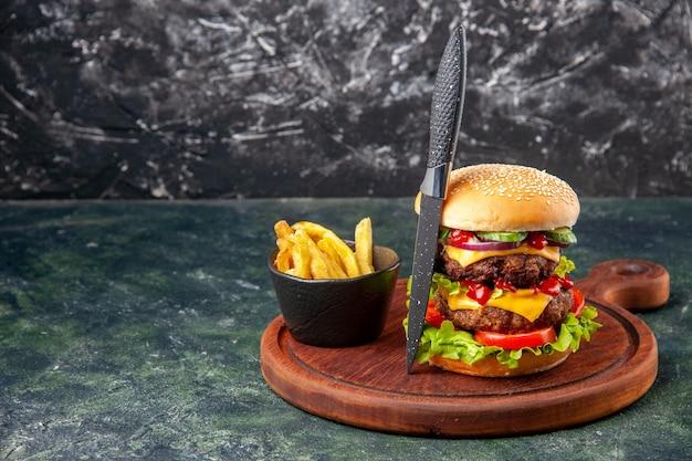 Leckeres hausgemachtes graues messer der sandwich-pommes auf holzschneidebrett auf der dunklen dunklen oberfläche der linken seite