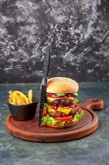 Leckeres hausgemachtes graues messer der sandwich-pommes auf schneidebrett auf dunkler farboberfläche